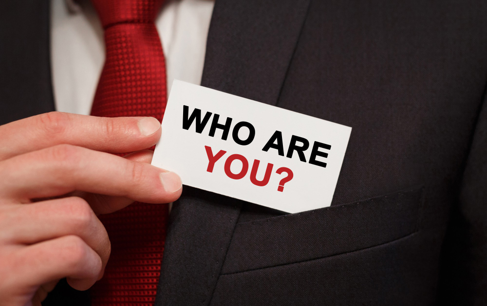 businessman-putting-card-with-text-who-are-you-pocket-1